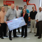 Britt Autry (BE'92), vice president, North American Production Promotion Center, DENSO Manufacturing Tennessee, presents a check to VUSE Associate Dean Cynthia Paschal. Back row, from left: Brian Crawford, DENSO senior specialist; Gary Walker, energetics lab manager; Dexter Watkins, mechanical engineering graduate student; Chris Lyne, mechanical engineering graduate student; and Amrutur Anilkumar, professor of the practice of aerospace engineering and mechanical engineering.