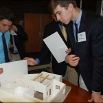 From left, Ryan Dick, Thomas Hardy and Nick Honkala assemble a model of Harmony House to be shown at a student research presentation.